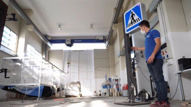 Un trabajador de Interlight junto a uno de los sistemas inteligentes de señalización vial