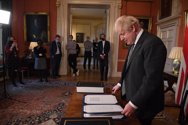 30 December 2020, England, London: UK Prime Minister Boris Johnson prepares to sign the EU-UK Trade and Cooperation Agreement at 10 Downing Street. Photo: Leon Neal/PA Wire/dpa