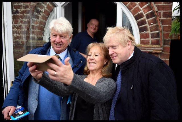 Boris Johnson junto a su padre, Stanley, se hacen una foto con una votante conservadora