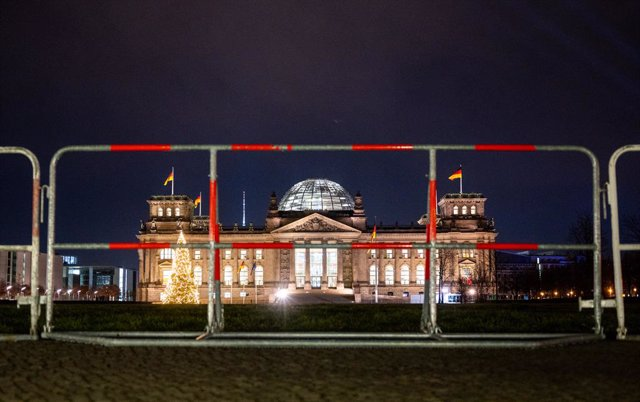 31 December 2020, Berlin: Barriers can be seen in front of the Reichstag building at the empty government district. Photo: Christophe Gateau/dpa