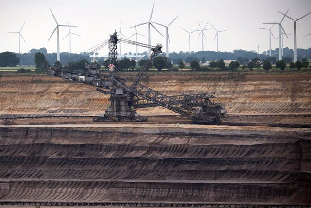 03 July 2020, North Rhine-Westphalia, Jackerath: Windmills rotate behind a bucket wheel excavator at the Garzweiler opencast lignite mine to generate electricity. Plans to phase out coal in Germany by 2038, including billions of euros in aid for the regio