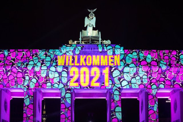 31 December 2020, Berlin: Projectors light up the Brandenburg Gate during the New Year's Eve celebrations. Germany's biggest New Year's Eve party at the Brandenburg Gate was cancelled this year due to coronavirus. Photo: Christoph Soeder/dpa