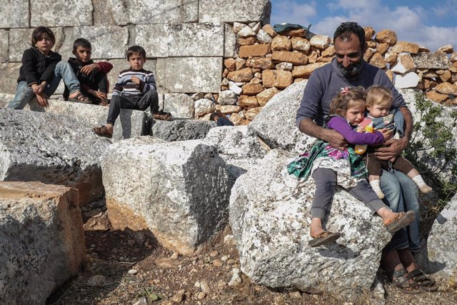 07 November 2020, Syria, Babisqa: A man sits with his children at the remains of an ancient church in the village of Babisqa. About 6 internally displaced Syrian families, whose homes in the village of Ain La Rose were destroyed by the Syrian government s