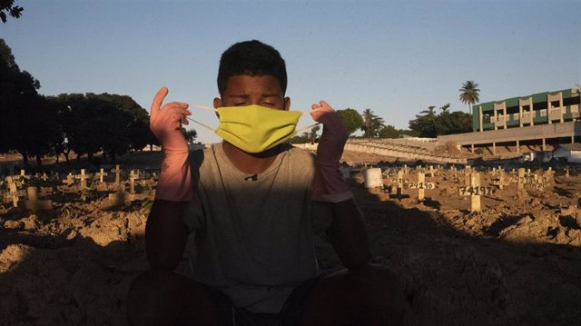Un joven trabajador de un cementerio de Río de Janeiro trabaja en el mantenimiento y desinfección de las lápidas para evitar posibles infecciones de coronavirus.