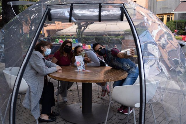 20 December 2020, Colombia, Bogota: A family sits inside a bubble-shaped gazebo installed by a restaurant in Bogota. Several restaurants in the city have installed gazebos to ensure a safe distance between customers. Photo: Natalia Ortiz Mantilla/dpa