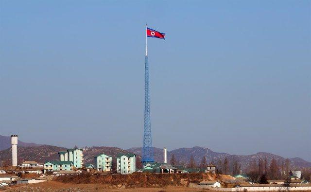 Una bandera de Corea del Norte ondeando sobre un edificio.