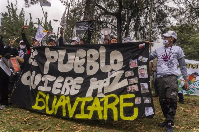 01 November 2020, Colombia, Bogota: Former combatants of the dissolved group Revolutionary Armed Forces of Colombia-People's Army (FARC) and social activists hold a banner during a march demanding that the current government guarantee their right to life