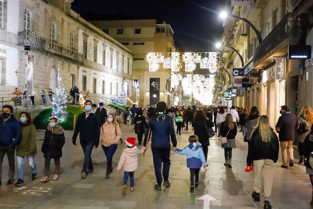 Transeúntes pasean bajo las luces navideñas, llevando mascarilla, alguno con gorro navideño, en Vigo, Galicia (España), a 25 de diciembre de 2020.
