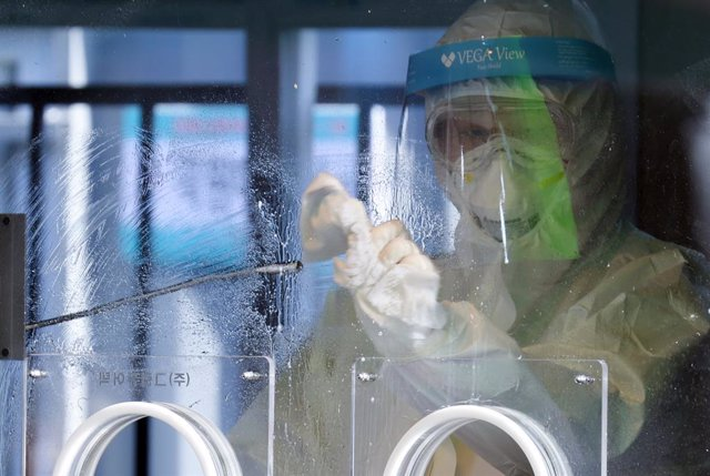 02 January 2021, South Korea, Seoul: A health worker disinfects a testing facility set up in front of Seoul station after conducting a coronavirus test. Photo: -/YNA/dpa