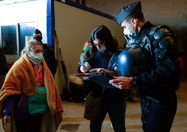 02 January 2021, France, Lieuron: French Gendarmes check ID's after breaking up a rave near a disused hangar in Lieuron about 40km south of Rennes. Some 2,500 partygoers attended an illegal New Year rave in northwestern France, violently clashing with pol