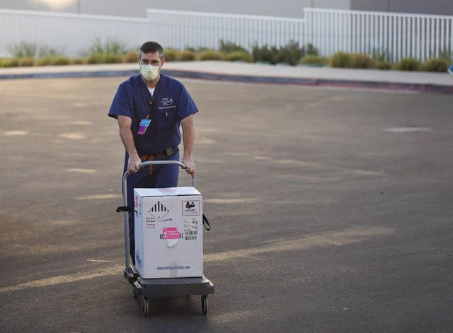 15 December 2020, US, San Diego: Rady Children's Hospital Pharmacy Manager Ron D'Ulisse wheels a shipment of the Pfizer-BioNTech COVID-19 vaccine into the hospital pharmacy. Photo: K.C. Alfred/San Diego Union-Tribune via ZUMA/dpa