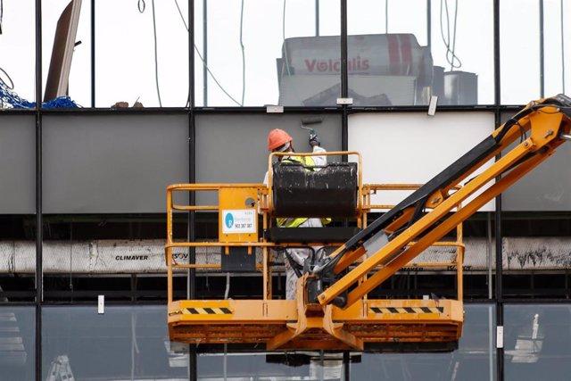 Un obrero trabaja desde una grúa en unas obras de Madrid