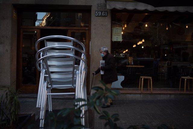 Cadires buides en una terrassa d'un cèntric carrer de Barcelona, Catalunya (Espanya), a 21 de desembre de 2020.