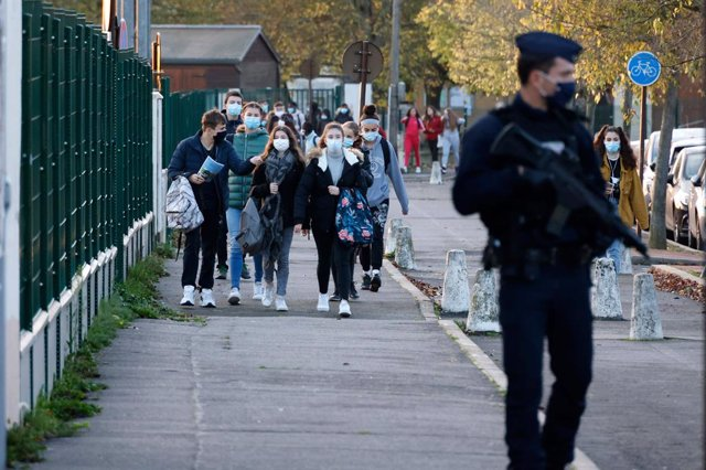 03 November 2020, France, Conflans-Sainte-Honorine: A CRS officer stands near the entrance of Le Bois d'Aulne middle school as the pupils are back to school after the holiday they took for two weeks following the killing of the French teacher Samuel Paty