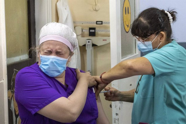29 December 2020, Argentina, Firmat: A health care worker of the San Martin Hospital receieves her dose of the Russian Sputnik V vaccine amid a nationwide vaccination campaign. Photo: Patricio Murphy/ZUMA Wire/dpa