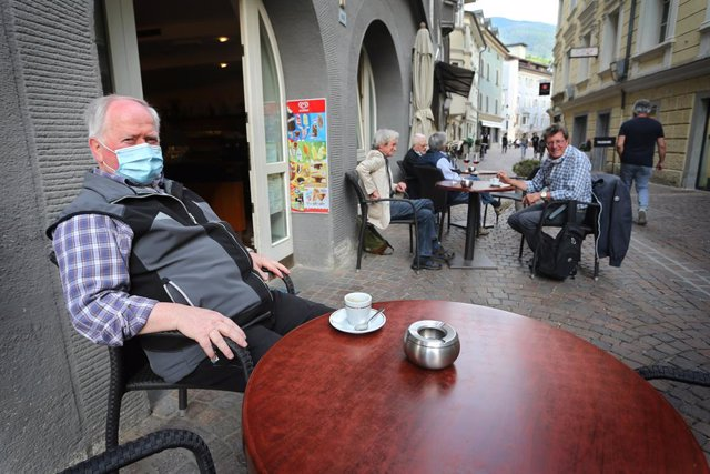 03 June 2020, Italy, Brixen: Aman wearing a face mask sits in a street cafe in the old town in Brixen. Italy on Wednesday reopened its borders to visitors from the rest of the European Union and dropped a ban on travel between its regions as part of the
