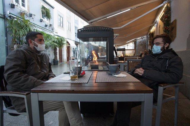 Dos jovenes toman una consumicion en una terraza