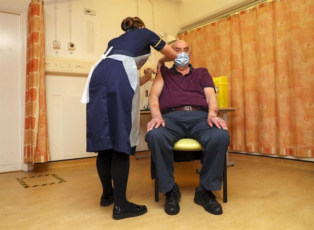 04 January 2021, England, Oxford: Brian Pinker, 82-year-old, receives the AstraZeneca/Oxford coronavirus (COVID-19) vaccine from nurse Sam Foster at the Churchill Hospital, he becomes the first person in the world to receive this vaccine. National Health
