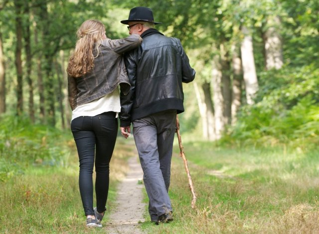 Padre e hija divirtiéndose al pasear por el bosque.