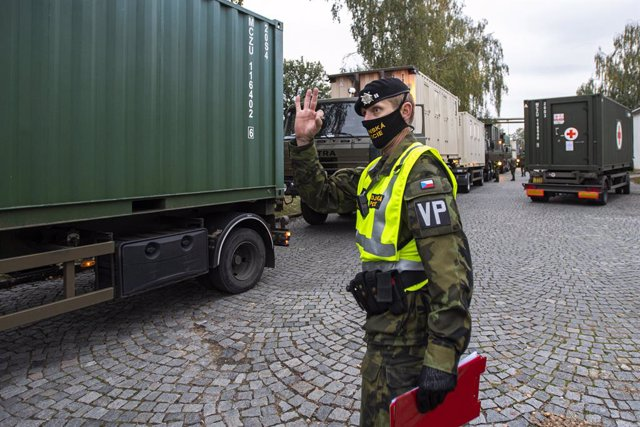 Soldado con mascarilla junto a un convoy militar para levantar un hospital de campaña en el recinto ferial de Praga, República Checa, para combatir el conronavirus