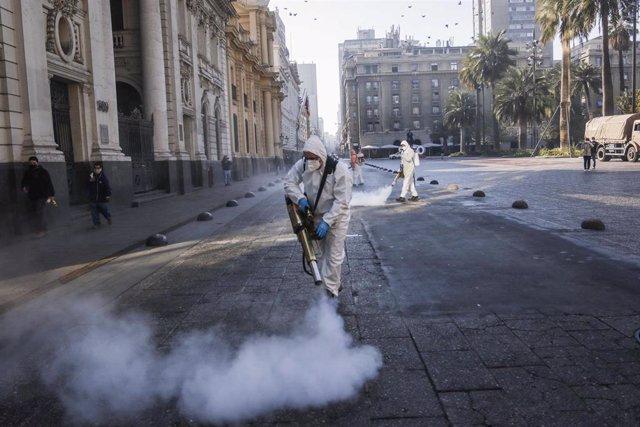 Trabajadores del Ayuntamiento de Santiago de Chile desinfectan una calle.