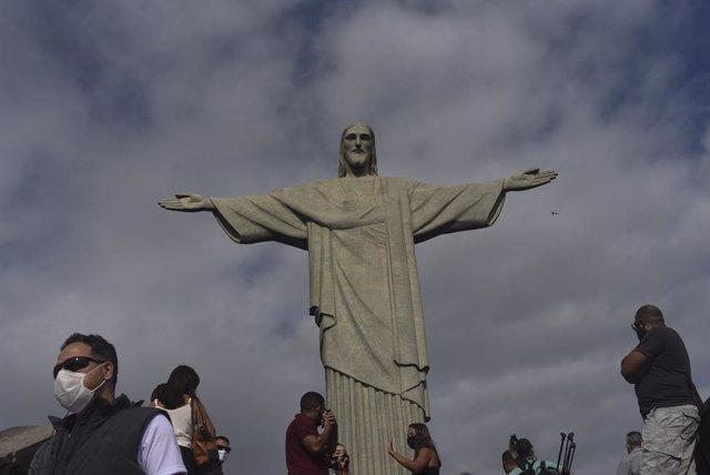 Personas con mascarilla por el coronavirus junto al Cristo del Corcovado de Río de Janeiro