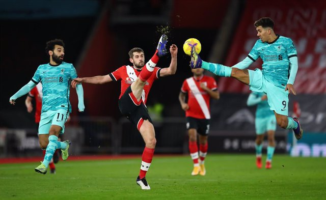 04 January 2021, England, Southampton: Southampton's Jack Stephens (C) and Liverpool's Roberto Firmino (R) battle for the ball during the English Premier League soccer match between Southampton and Liverpool at St Mary's Stadium. Photo: Michael Steele/PA
