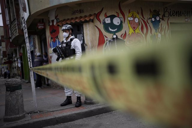 13 July 2020, Colombia, Bogota: A Colombian police member wears protective suits as he stands guard during a curfew imposed to curb the spreading of coronavirus. Photo: Sergio Acero/colprensa/dpa