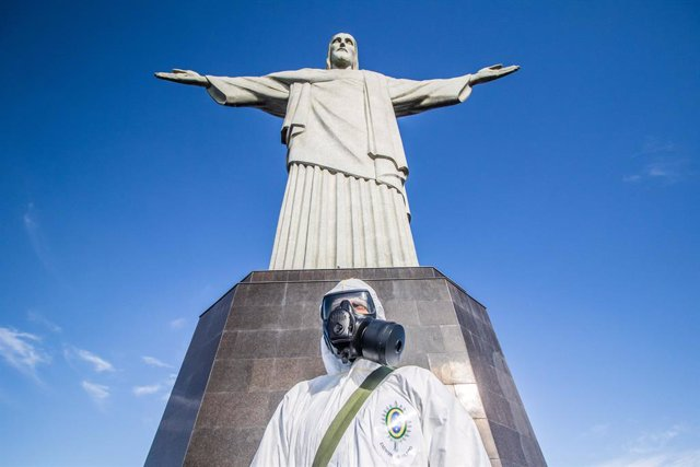 13 August 2020, Brazil, Rio de Janeiro: A military member wears a coverall suit and a face mask stands in front of the statue of Christ the Redeemer, during a disinfection process for the main tourist spot in Rio de Janeiro which will be reopened next wee