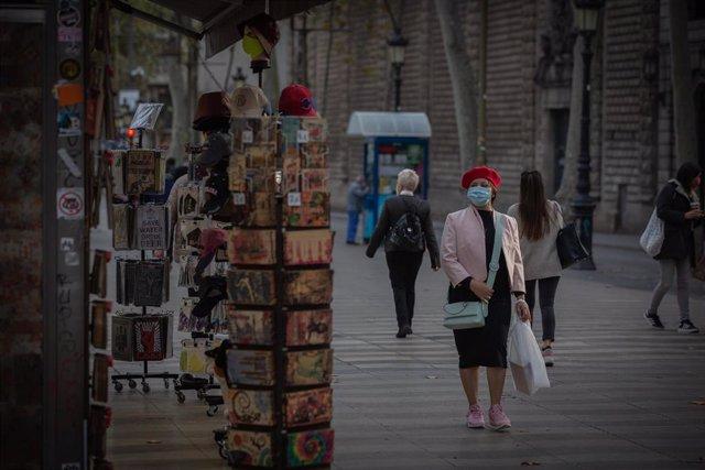 Una mujer frente a una tienda de artículos turísticos en Barcelona, Catalunya (España), a 16 de noviembre de 2020. El turismo internacional se desplomó este verano debido como consecuencia del coronavirus. Además, el pasado 15 de octubre el Govern de la G