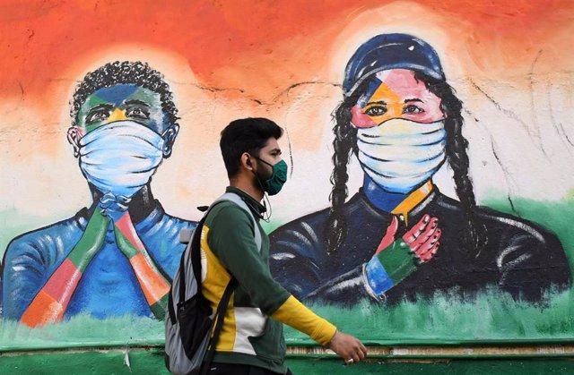 Un hombre con mascarilla delante de un grafiti en India durante la pandemia de coronavirus