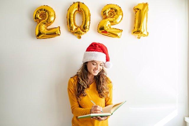 Mujer apuntando sus propositos de año nuevo.