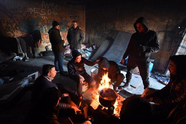 Refugiados egipcios a los pies de un fuego improvisado para protegerse del frío en el campamento de Lipa, en Bihac, ciudad situada en el noroeste de Bosnia y Herzegovina.