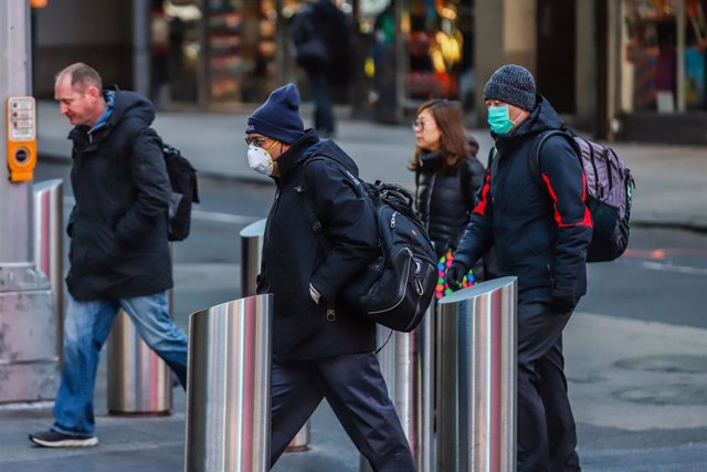 16 March 2020, US, New York: People wearing medical masks to prevent the Coronavirus (Covid-19) are seen walking in Times Square. Photo: Vanessa Carvalho/ZUMA Wire/dpa