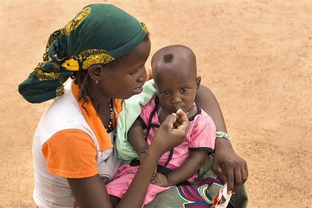 Una madre da de comer a su hijo desnutrido en Burkina Faso