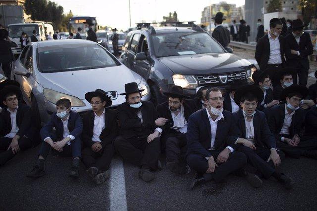 27 December 2020, Israel, Bnei Brak: Ultra-Orthodox Jews block a road during a demonstration staged moments before Israel enters its thirdnationwide lockdown amid the coronavirus pandemic. Photo: Ilia Yefimovich/dpa