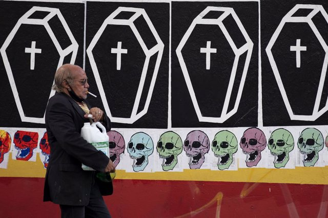 05 January 2021, Brazil, Sao Paulo: A man with a lowered face mask walks past a graffiti showing coffins at a street in Sao Paulo. Photo: Marcelo Chello/ZUMA Wire/dpa