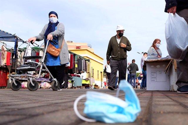 Una mascareta quirúrgica a terra mentre diverses persones caminen.