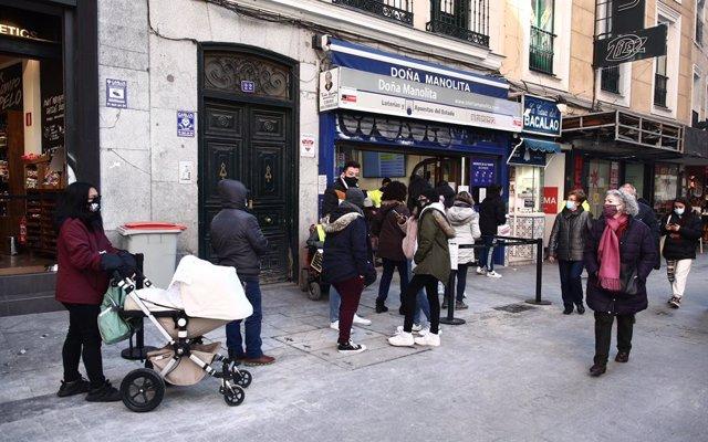 Diverses persones fan cua davant l'administració de loteria Doña Manolita, a Madrid (Espanya), 5 de gener del 2021