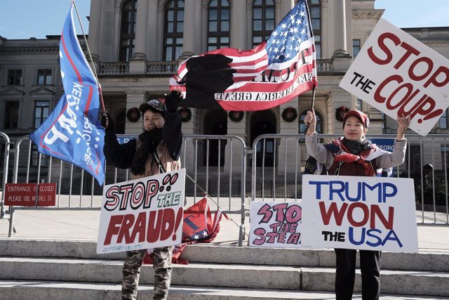 19 December 2020, US, Atlanta: Two demonstrators hold placards on the steps of the Georgia Capitol building in Atlanta during a rally to support US President Donald Trump. Photo: John Arthur Brown/ZUMA Wire/dpa