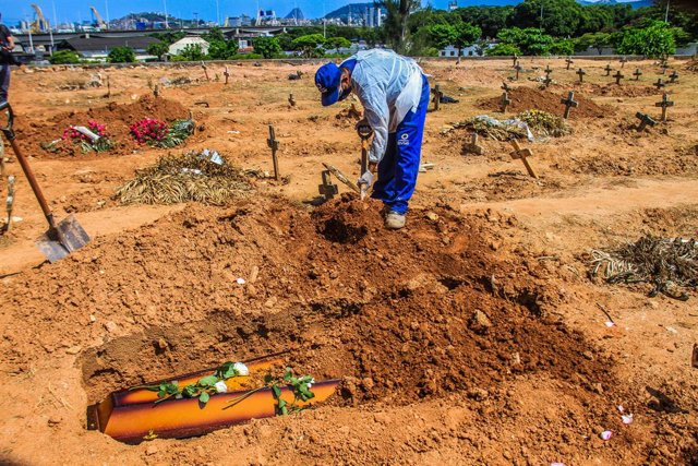 16 December 2020, Brazil, Rio de Janeiro: A cemetery worker in protective suits buries the body of a man who died from the coronavirus (COVID-19) at Sao Francisco Xavier cemetery. Photo: Ellan Lustosa/ZUMA Wire/dpa