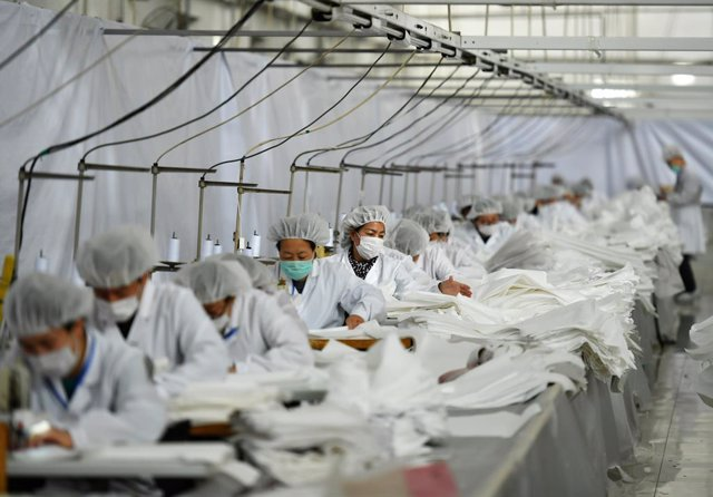 FILED - 17 February 2020, China, Shijiazhuang: Employees wear protective suits as they work to produce more than 25000 protective suits every day to send them to Wuhan during the current Coronavirus outbreak. Photo: -/TPG via ZUMA Press/dpa