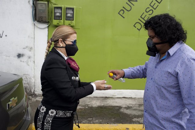 """21 June 2020, Ecuador, Quito: A man hands disinfectant to a musician of the Mariachi group """"Mariachis a la Mexicana"""" during the celebrations of the Father's Day, due to the ongoing coronavirus pandemic. Photo: Juan Diego Montenegro/dpa"""
