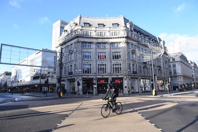 20 December 2020, England, London: A cyclist rides in the almost deserted Oxford Circus shopping street. British Prime Minister Boris Johnson announced a strict lockdown and cancelled Christmas holiday gatherings across London and eastern and south-east E