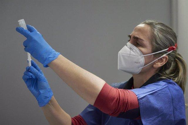 Una trabajadora sanitaria, con material necesario para administrar la vacuna contra la COVID-19, en una imagen de archivo