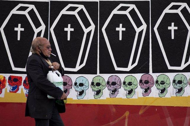 Un hombre camina frente a un mural con ataúdes en Sao Paulo, Brasil.
