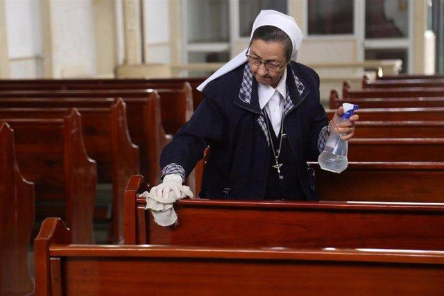 Una monja desinfecta los bancos de una iglesia en Colombia.