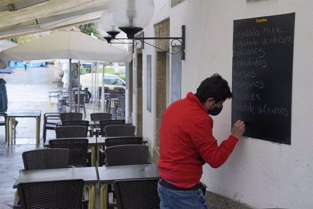 Un hombre escribe en la pizarra de un mesón, en Santiago de Compostela, A Coruña, Galicia (España), a 4 de diciembre de 2020. Hoy se reabre la hostelería en toda Galicia, aunque en distinto grado en función de los datos de los contagios de coronavirus, y