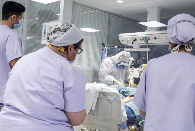 Trabajadores sanitarios totalmente protegidos atienden a un paciente con coronavirus ingresado en la UCI (archivo)
