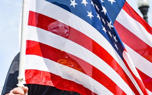 22 August 2020, US, Davenport: A masked man is seen through an American flag during an 'American patriot 2A March' near Modern Woodmen Park. Photo: Meg Mclaughlin/Dispatch Argus via ZUMA Wire/dpa